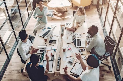 Top_view_of_multiracial_young_creative_people_in_modern_office._Group_of_young_business_people_are_working_together_with_laptop,_tablet,_smart_phone,_notebook._Successful_hipster_team_in_coworking._Freelancers.