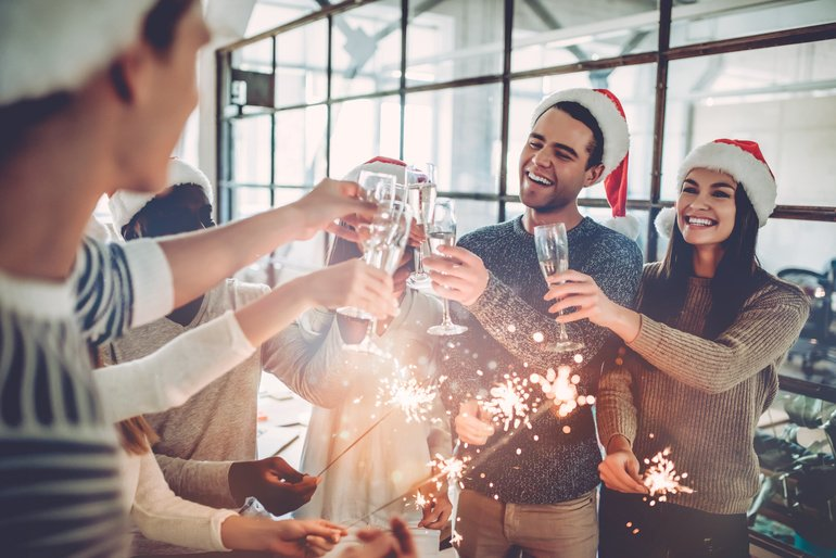 Merry_Christmas_and_Happy_New_Year_2018!Multiracial_young_creative_people_are_celebrating_holiday_in_modern_office._Group_of_young_business_people_are_drinking_champagne_with_sparkling_bengal_lights_in_coworking._Successful_hipster_team_of_freelancers.