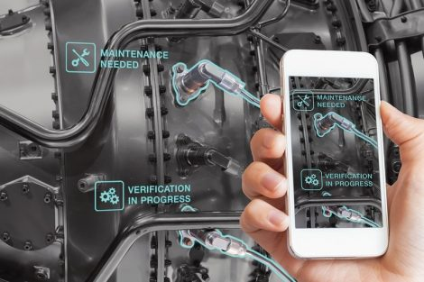 Augmented_Reality_technology_maintenance_and_service_of_mechanical_parts,_technician_using_smartphone_with_AR_interface_on_screen_in_smart_industry,_automated_monitoring_process