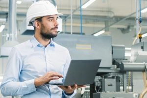 Chief_Engineer_in_the_Hard_Hat_Walks_Through_Light_Modern_Factory_While_Holding_Laptop._Successful,_Handsome_Man_in_Modern_Industrial_Environment.