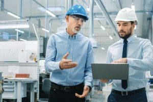 Head_of_the_Department_Holds_Laptop_and_Discuss_Product_Details_with_Chief_Engineer_while_They_Walk_Through_Modern_Factory.