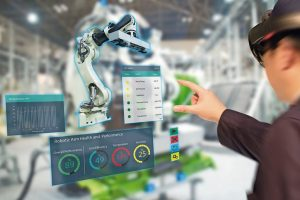 iot_industry_4.0_concept,industrial_engineer(blurred)_using_smart_glasses_with_augmented_mixed_with_virtual_reality_technology_to_monitoring_machine_in_real_time.Smart_factory_use_Automation_robot_arm
