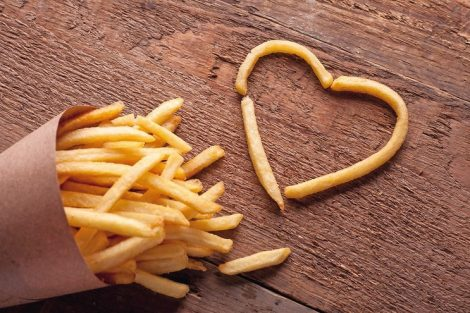 I_love_fried_potatoes._French_fries_in_a_paper_box_and_symbol_of_a_heart_on_a_wooden_table