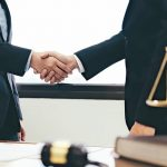 Law_and_Legal_services_concept._Lawyer_and_attorney_having_team_meeting_at_law_firm._Lawyer_and_businessman_handshake.