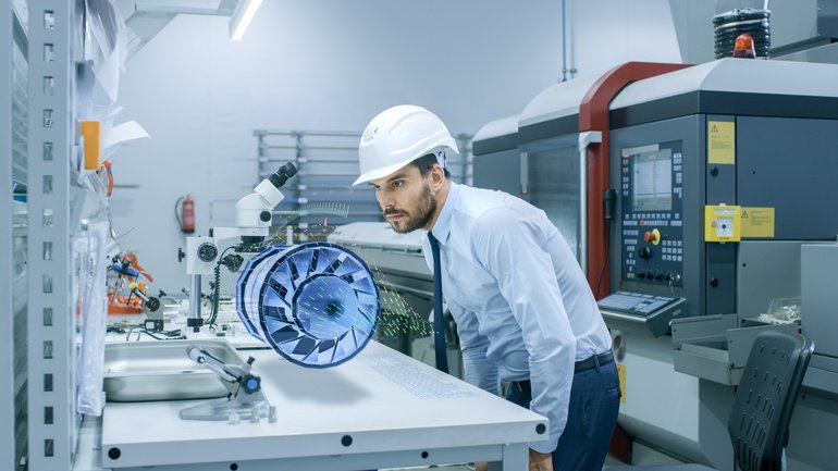 In_High_Tech_Futuristic_Factory_Chief_Engineer_Works_with_Holographic_Projection_3D_Model_of_the_Engine_Turbine_Prototype._Futuristic_Desing_of_Virtual_Mixed_Reality_Application.