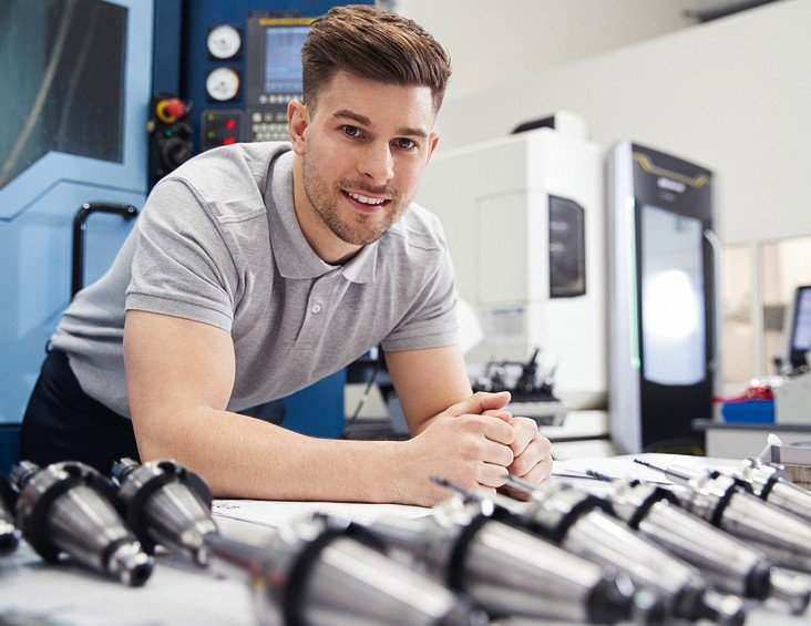 Portrait_Of_Male_Engineer_With_CAD_Drawings_In_Factory