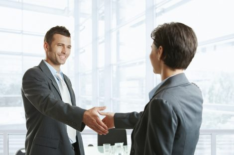 Smiling_businessman_greeting_businesswoman_with_handshake_before_meeting.