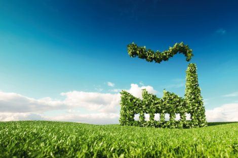 Eco_friendly_industry_concept._3d_rendering_of_green_factory_icon_on_fresh_spring_meadow_with_blue_sky_in_background.