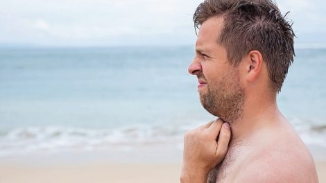 Worried_caucasian_man_sucking_his_thumb_standing_on_the_tropical_beach._Profile_view