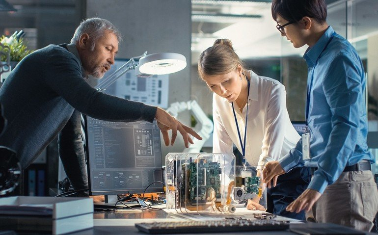 Team_of_Computer_Engineers_Lean_on_the_Desk_and_Choose_Printed_Circuit_Boards_to_Work_with,_Computer_Shows_Programming_in_Progress._In_The_Background_Technologically_Advanced_Scientific_Research_Center.