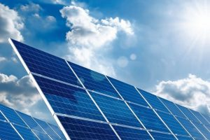 Two_large_solar_panels_under_the_blue_sky_with_the_sun_and_clouds
