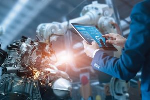Manager_engineer_check_and_control_automation_robot_arms_machine_in_intelligent_factory_industrial_on_real_time_monitoring_system_software._Welding_robotics_and_digital_manufacturing_operation._