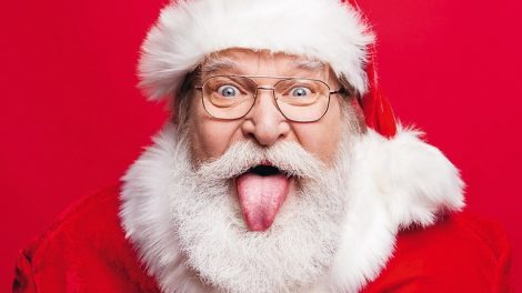 Best_party_time_concept._Close_up_portrait_of_aged_stylish_cheerful_Saint_Nicholas_with_sticking_tongue_out_look_at_camera_fooling_around_isolated_on_noel_vivid_red_background
