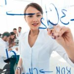 view_through_the_transparent_Board._female_scientist_makes_a_report_to_colleagues._concept_of_research_view_through_the_transparent_Board._female_scientist_makes_a_report_to_colleagues._concept_of_research