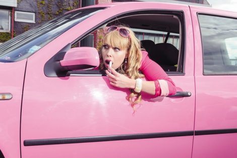 Junge_blonde_Frau_in_pinken_Klamotten_sitzt_in_einem_pinken_PKW_und_zieht_sich_den_Lippenstift_im_Außenspiegel_nach.