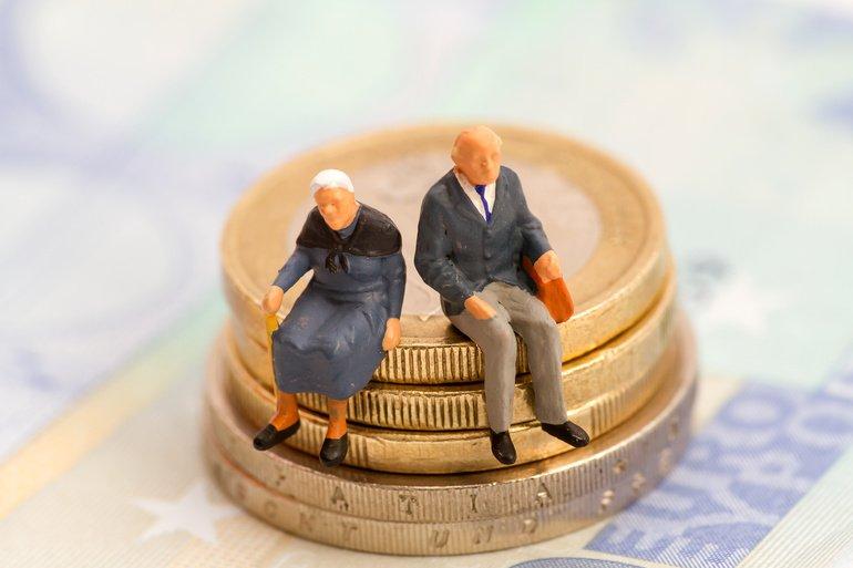 Senioren_sitzen_auf_Muenzstapel