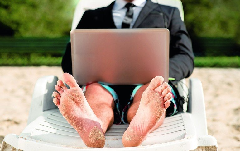 Businessman_dressed_in_suit_and_shorts_working_with_laptop_on_the_sunbed_at_the_beach