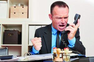 Wütender_Geschäftsmann_brüllt_im_Büro_ins_Telefon_am_Schreibtisch