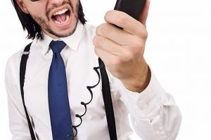 Angry_businessman_with_phone_isolated_on_white