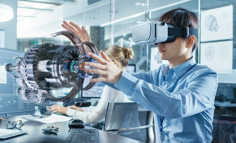 Computer_Science_Engineer_wearing_Virtual_Reality_Headset_Works_with_3D_Model_Hologram_Visualization,_Makes_Gestures._In_the_Background_Engineering_Bureau_with_Busy_Coworkers.