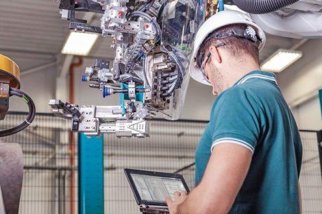 Maschinenbau_Ingenieur_mit_Schutzhelm_und_Notebook_bei_der_Inbetriebnahme_eines_Roboters