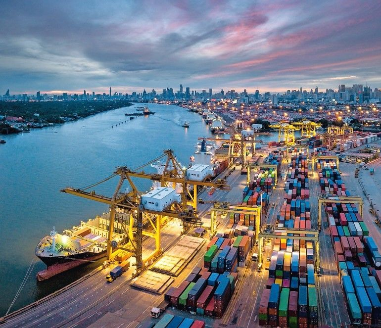 Aerial_view_of_international_port_with_Crane_loading_containers_in_import_export_business_logistics_with_cityscape_of_Bangkok_city_Thailand_at_night