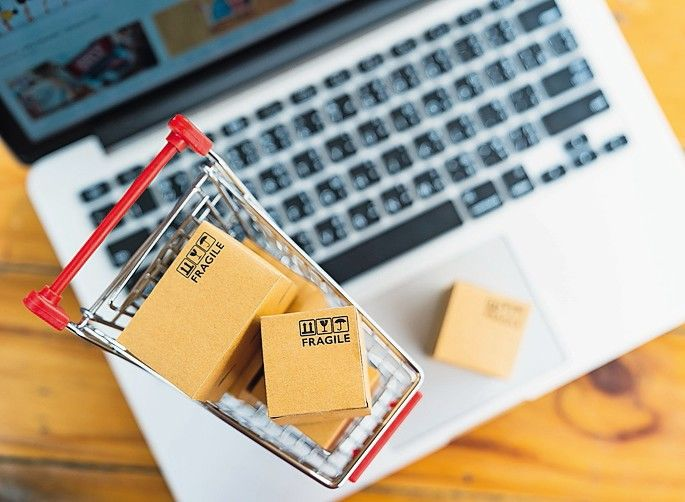 Top_view_of_product_package_boxes_in_cart_with_laptop_computer_on_table_for_online_shopping_and_delivery_concept
