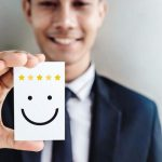 Customer_Experience_Concept,_Happy_Businessman_holding_Card_with_Smiley_Face_and_Five_Star_Rating_for_his_Satisfaction