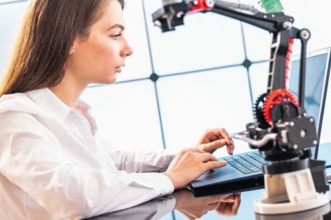 A_young_woman_writes_an_algorithm_for_the_robot_arm._Science_Research_Laboratory_for_Robotic_Arm_Model._Computer_Laboratory