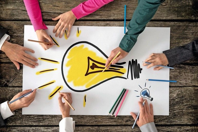 Top_view_of_six_people,_men_and_women,_drawing_bright_yellow_light_bulb_on_a_large_sheet_of_paper_or_placard._Conceptual_of_teamwork,_research,_education_and_innovation.