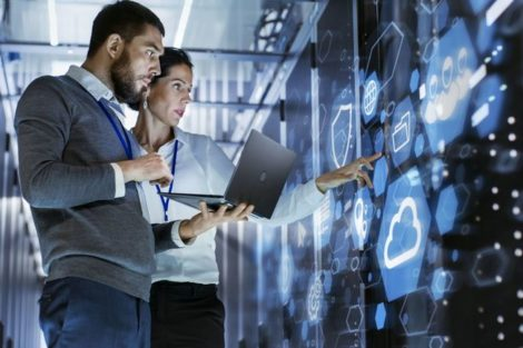 Male_IT_Specialist_Holds_Laptop_and_Discusses_Work_with_Female_Server_Technician._They're_Standing_in_Data_Center,_Rack_Server_Cabinet_with_Cloud_Server_Icon_and_Visualization.