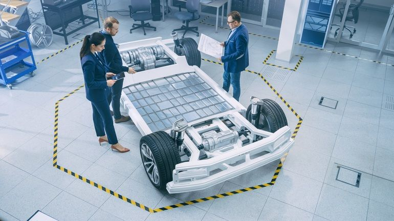 Automotive_Design_Engineers_Talking_while_Working_on_Electric_Car_Chassis_Prototype._In_Innovation_Laboratory_Facility_Concept_Vehicle_Frame_Includes_Wheels,_Suspension,_Engine_and_Battery.