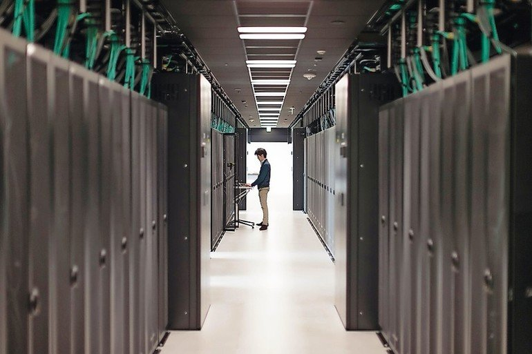 Profile_silhouette_of_man_typing_on_computer_near_high_tech_cabinet_in_server_room