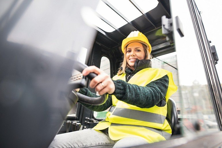 Female_forklift_truck_driver_in_an_industrial_area._A_woman_sitting_in_the_fork_lift_outside_a_warehouse.