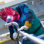 Industrial_worker_with_protective_mask_welding_inox_elements_in_steel_structures_manufacture_workshop.