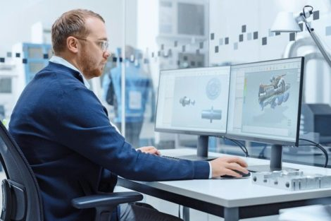 Male_Industrial_Engineer_Solving_Problems,_Working_on_a_Personal_Computer,_Two_Monitor_Screens_Show_CAD_Software_with_3D_Prototype_of_Hybrid_Electric_Engine_Being_Tested._Working_Modern_Factory