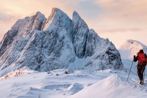 Mountaineer_man_climbs_on_top_snowy_mountain_with_colorful_sky_in_morning