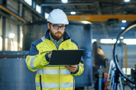 Industrial_Engineer_in_Hard_Hat_Wearing_Safety_Jacket_Uses_Laptop._He_Works_in_the_Heavy_Industry_Manufacturing_Factory_with_Various_Metalworking_Processes_are_in_Progress.