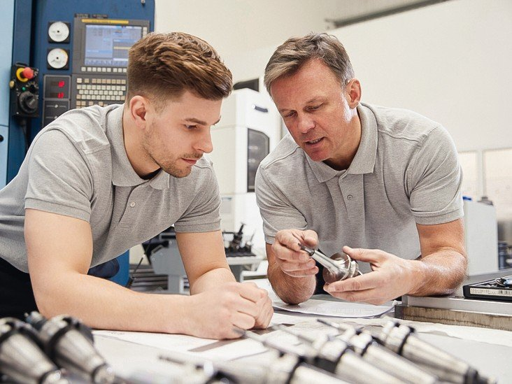 Engineer_Showing_Apprentice_How_To_Measure_CAD_Drawings
