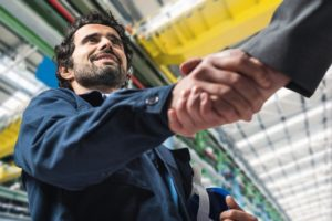 Portrait_of_a_man_giving_an_handshake_in_an_industrial_facility
