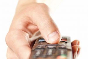 Hand_holding_the_TV_remote._Close_up._Isolated_on_white_background.