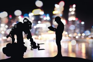 Industry_4.0_technology_,_artificial_intelligence_trend_concept._Silhouette_of_engineer_man_control_to_heavy_automation_robot_arm_machine._Bokeh_flare_light_effect_with_building_background.
