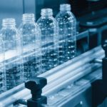 The_plastic_bottles_on_the_conveyor_belt_at_the_drinking_water_factory._Drinking_water_manufacturing_process.