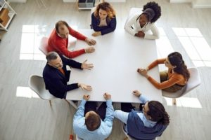 Group_of_diverse_business_people_sitting_around_big_modern_square_office_table._High_angle_shot_of_team_of_mixed_race_company_employees_discussing_work_matters_in_corporate_meeting
