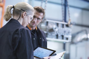 Engineers_inspect_plans_on_digital_tablet_in_engineering_factory