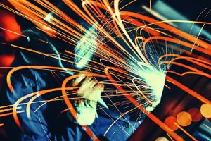 Unrecognizable_man_welding_metal_plate_and_construction_frame._This_is_arc_welding.The_worker_is_using_protective_mask_and_blue_working_uniform._Background_is_lit_orange._Long_exposure.