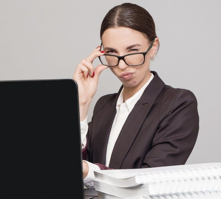 Cheerful_business_woman_sitting_at_the_desk_with_papers_and_books_and_using_laptop