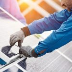 Smiling_male_technician_in_blue_suit_installing_photovoltaic_blue_solar_modules_with_screw._Man_electrician_panel_sun_sustainable_resources_renewable_energy_source_alternative_innovation