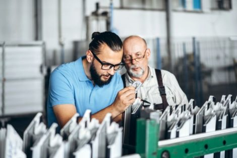 Young_manager_with_beard_showing_and_inspecting_working_process_of_adult_professional_worker_on_the_big_factory