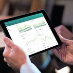 Business_person_analyzing_financial_statistics_displayed_on_the_tablet_screen._Close_up_of_businessman_analyzing_chart_on_digital_tablet._Closeup_of_man_hands_holding_digital_tablet_and_looking_a_stock_market_reports.